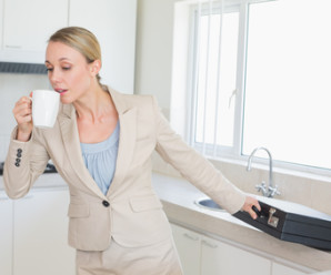 Businesswoman rushing out the door to work in the morning at home in the kitchen